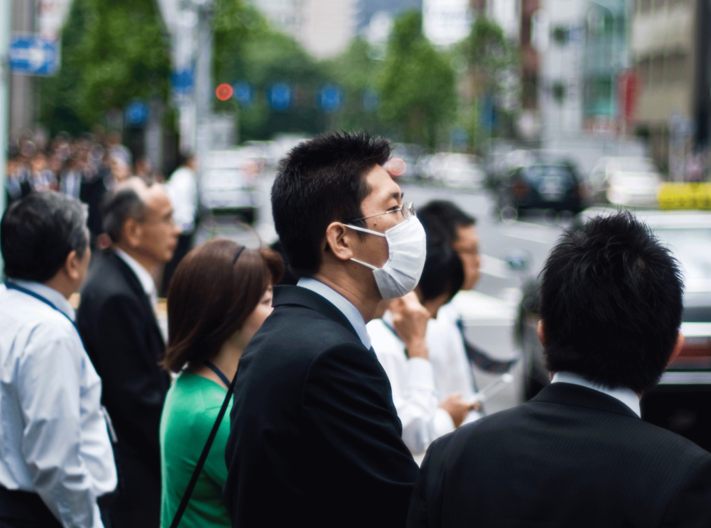Picture of a group of people by a road, one with a mask over his mouth