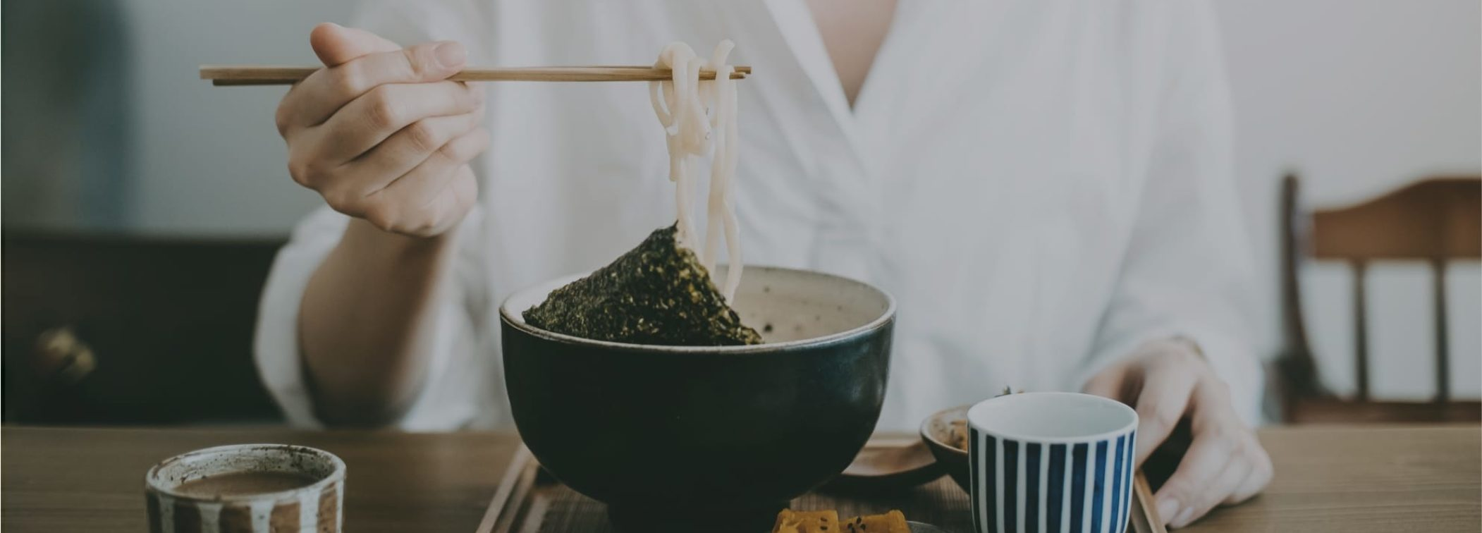 Photo of a bowl of noodles being eaten with chopsticks